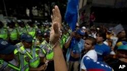 Seorang demonstran mengangkat tangannya yang memegang rosario, dalam protes menentang pemerintah di Caracas, Venezuela (23/1). (AP/Fernando Llano)
