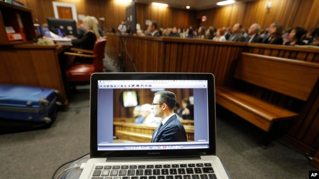 Oscar Pistorius is viewed on a laptop as he sits in the dock in court in Pretoria, South Africa, March 14, 2014.
