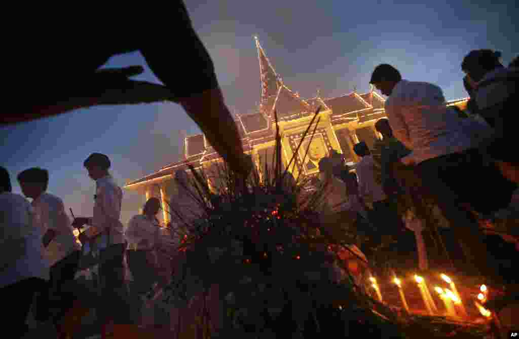 Mourners burn incense and offer prayers at the Royal Palace displaying a portrait of their former King Norodom Sihanouk in Phnom Penh, Cambodia, Wednesday Oct. 17, 2012. The body of Sihanouk returned to his homeland on a plane from China on Wednesday, wel