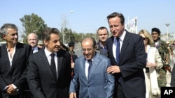 From left: French philosopher Bernard-Henri-Levy, France's President Nicolas Sarkozy, NTC PM Mahmoud Jibril, and Britain's PM David Cameron arrive at the Tripoli Medical Center, Sep 15, 2011.
