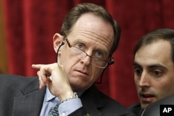 FILE - Sen. Patrick Toomey, R-Pa., left, confers with an aide, on Capitol Hill.