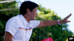 "FILE - Vice-presidential candidate Sen. Ferdinand ""Bongbong"" Marcos Jr. waves to supporters during his campaign sortie in Muntinlupa city, southeast of Manila, Philippines, Feb. 22, 2016."