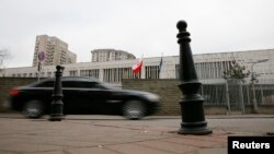 A car drives past a building of the Polish Embassy in Moscow, Nov. 17, 2014.