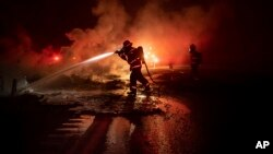 Seorang anggota pemadam kebakaran menyemprotkan puing-puing kendaraan yang masih membara di jalan raya Interstate 5 di kawasan Hutan Taman Nasional Shasta-Trinity, California pada tanggal 5 September 2018 (foto: AP Photo/Noah Berger)