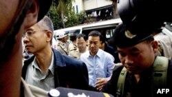 Nhân viên an ninh Kampuchia hộ tống nhà hoạt động Thái Lan Veera Somkwamkid, thứ hai từ trái sang, và ông Panich Vikitsreth, Đại biểu Quốc hộ Thái, đến Tòa án thành phố Phnom Penh