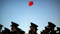 FILE - Chinese paramilitary police stand in formation after a flag raising ceremony at Tiananmen Square on National Day. Methods of torture outlined by Amnesty include beatings, sleep deprivation, being forced into painful positions for long periods, and