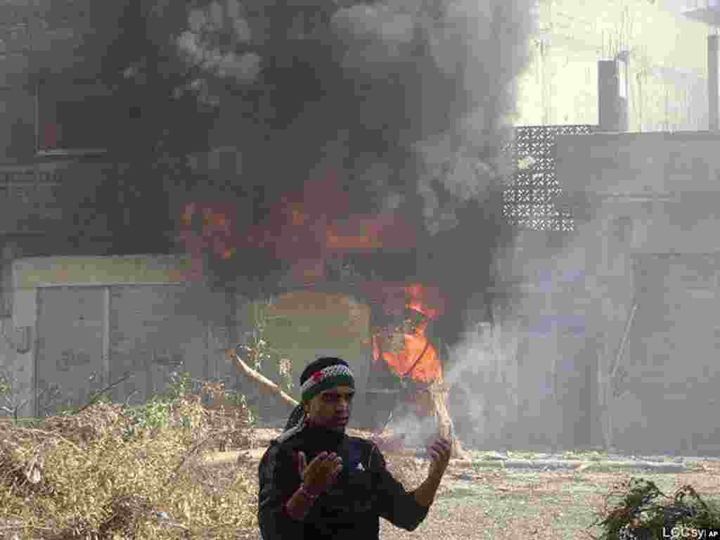 An anti-Syrian regime man reacts in front of flames which rise from a burning shop damaged by Syrian government forces shelling, in Baba Amr neighborhood in Homs province, central Syria, February 12, 2012. (AP/Local Coordination Committees in Syria)