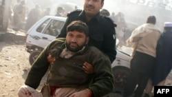 Nhân viên an ninh Pakistan khiêng người bị thương ra khỏi hiện trường sau vụ nổ bom ở khu vực bộ tộc trong vùng Khyber gần Peshawar, ngày 10/1/2012