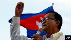 FILE: Cambodian opposition leader Sam Rainsy of the Cambodia National Rescue Party delivers a speech before his party supporters during a rally in Phnom Penh, Cambodia, Sunday, Dec. 22, 2013.