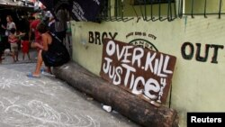 "A sign reading ""Overkill Justice for Eric"" is displayed at the entrance of a street where Eric Quintinita Sison was killed in Pasay city, Metro Manila in the Philippines, Aug. 29, 2016. Family members of Sison said he was attempting to surrender when he was gunned down by police during a meth bust."