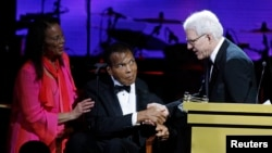 Honoree Steve Martin (R) accepts his award from Muhammed and Lonnie Ali at the Muhammad Ali Celebrity Fight Night Awards XIX in Phoenix, Arizona March 23, 2013. The charity event is held in honor of Muhammad Ali's fight to find a cure for Parkinson's dise