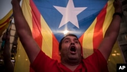 "A pro-independence supporter holds up a ""estelada"" or pro independence flag as crowds gather in the square outside the Palau Generalitat in Barcelona, Spain, on Friday, Oct. 27, 2017. (AP Photo/Santi Palacios)"