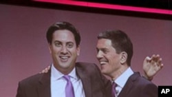 Ed Miliband, left, newly-elected leader of Britain's opposition Labour Party, embraces his brother David Miliband, following David's speech on foreign policy during the party's annual conference, in Manchester, England. Labour elected young lawmaker Ed Mi
