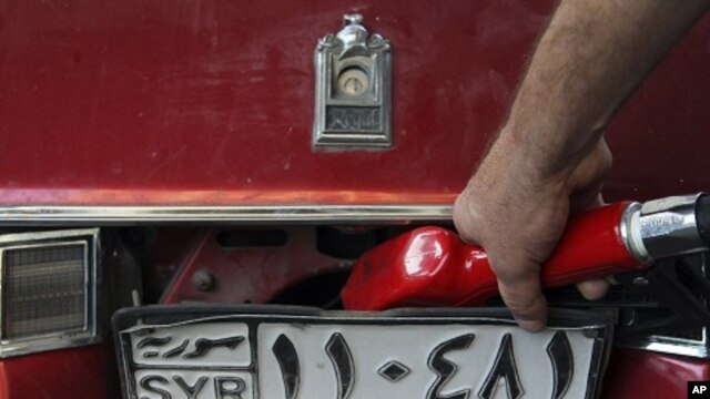 A Syrian gas station attendant fills up a car in Damascus (file photo)