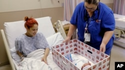 Infant Sleep Recommendations: FILE - In this May 6, 2016, file photo, Keyshla Rivera smiles at her newborn son Jesus as registered nurse Christine Weick demonstrates a baby box before her discharge from Temple University Hospital in Philadelphia on Friday, May 6, 2016.