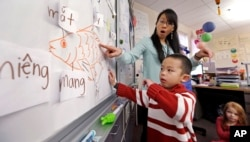 In this photo taken Feb. 14, 2014, kindergarten teacher Thao Tran helps student Brian Ho learn fish-related words in Vietnamese in a dual immersion language class at White Center Heights Elementary School in Seattle, Washington (AP Photo/Elaine Thompson)