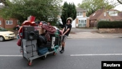 FILE - A squatter moves his belongings after being evicted from a housing estate in north London, Britain Sept. 24, 2015. The richest Britons are accumulating wealth three times as fast as the poorest, according to new official data.