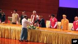 លោកប្រធានាធិបតីមីយ៉ាន់ម៉ា Thein Sein ចាប់ដៃជាមួយមេដឹកនាំរបស់ក្រុមជនជាតិភាគតិចប្រដាប់អាវុធក្នុងពិធីចុះហត្ថលេខាលើ «បទឈប់បាញ់គ្នាថ្នាក់ជាតិ» នៅមជ្ឈមណ្ឌល Myanmar International Convention Center កាលពីថ្ងៃទី១៥ ខែតុលា ឆ្នាំ២០១៥ ក្នុងក្រុងណៃពិដោ (Naypyitaw) ប្រទេសមីយ៉ាន់ម៉ា។