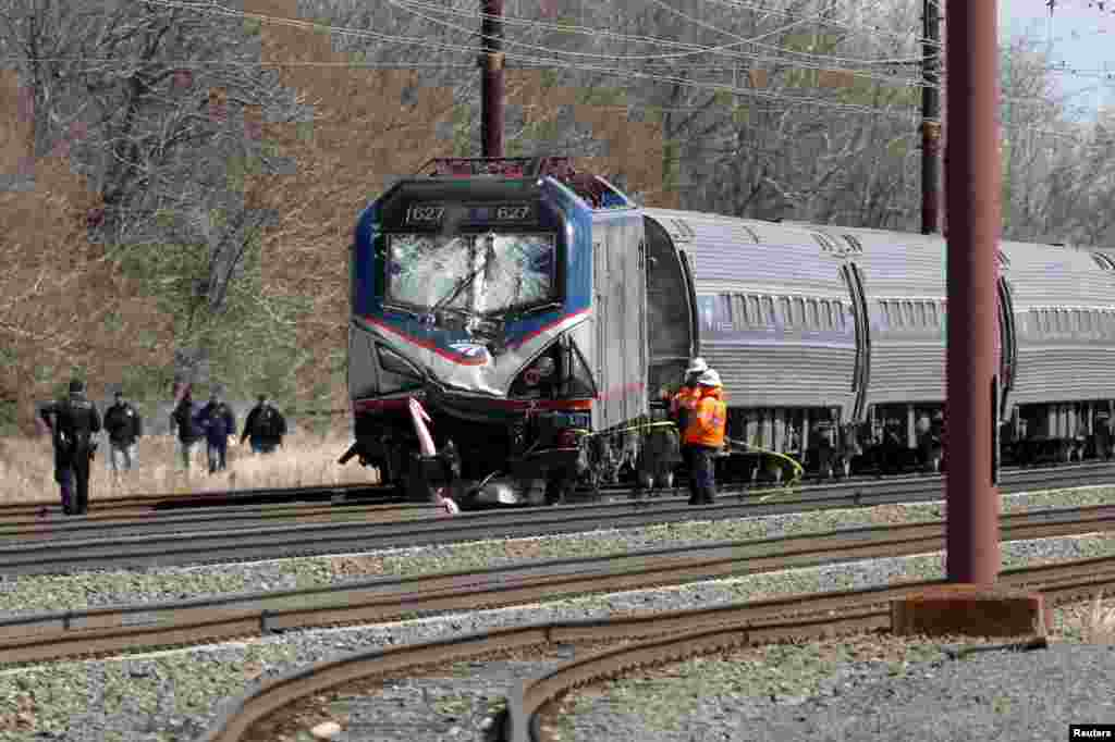 Emergency personnel examine the scene after an Amtrak passenger train struck a backhoe, killing two people, in Chester, Pennsylvania. The southbound Palmetto train running from New York to Savannah, Georgia, had about 341 passengers and seven crew members aboard when it struck the backhoe.