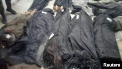 Covered dead bodies lie on the ground after Islamic State fighters killed 20 people in the village of Aqarib al-Safi, east of Hama city, Syria in this handout picture provided by SANA on May 18, 2017.
