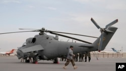 An Afghan soldier walks past Indian-donated helicopters to Afghanistan at the Kabul airport in Kabul, Dec. 25, 2015. India donated four Mi-25 attack helicopters to the Afghanistan Air Force.