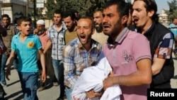 敘利亞戰機星期三襲擊了北部城市阿勒頗﹐親友將受害者屍體運走。