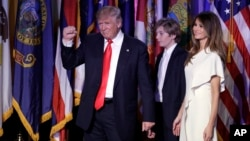 President-elect Donald Trump pumps his fist after giving his acceptance speech as his wife Melania Trump, right, and their son Barron Trump follow him during his election night rally in New York, Nov. 9, 2016.
