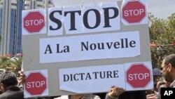 """一名前政权的支持者在突尼斯的集会上举起标语牌,抗议即将举行的选举,标语牌上写着""""制止新的独裁统治"""""""