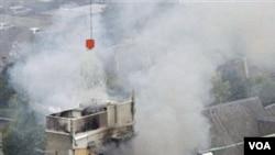 Regu penyelamat berusaha memadamkan asap dari sebuah gedung yang runtuh akibat gempa di Christchurch, Selandia Baru.