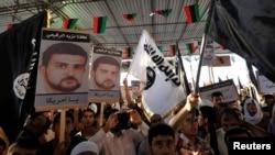 利比亚人在班加西举着利比的画像抗议美国抓捕利比。(2013年10月11日)