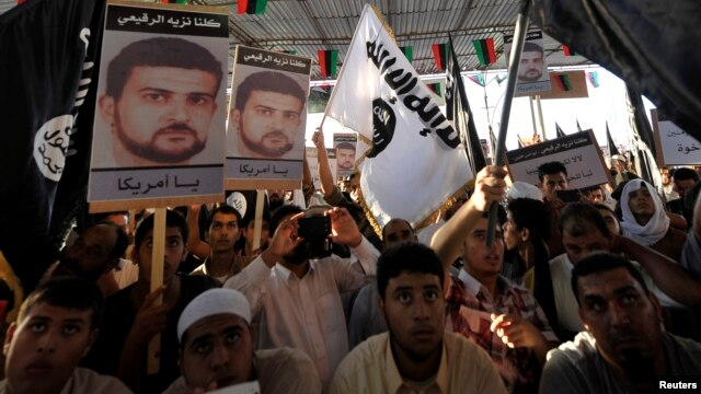 People hold posters of senior al Qaida figure Abu Anas al-Libi (L) during a demonstration over his capture by U.S. authorities, in Benghazi, Oct. 11, 2013.