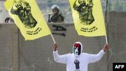 یک معترض فلسطینی در رام الله پرچم هایی دارد که عکس «مروان برغوثی» زندانی محکوم به ابد روی آن چاپ شده است.