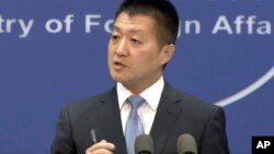 FILE - Lu Kang, spokesman of the Chinese Ministry of Foreign Affairs, speaks to reporters during a news briefing in Beijing, July 12, 2016.