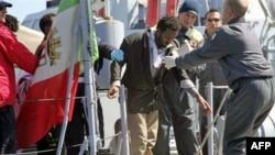 Một di dân được đưa lên bờ từ tàu của đội Tuần duyên Ý