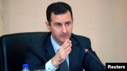 Syria's President Bashar al-Assad heads a Cabinet meeting in Damascus, in this handout photograph distributed by Syria's national news agency SANA on Feb. 12, 2013.