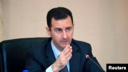 Syria's President Bashar al-Assad heads a Cabinet meeting in Damascus, in this handout photograph distributed by Syria's national news agency SANA, February 12, 2013.