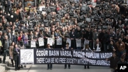Hundreds of Turkish journalists, some holding photos of recently jailed journalists, march to protest the detention of journalists in an alleged coup plot and demand reforms to Turkey's media laws, in Ankara, Turkey, Mar. 19, 2011.