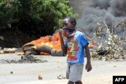 Un enfant se couvre la bouche pour se protéger de la fumée, Lusaka, Zambie, le 12 janvier 2018