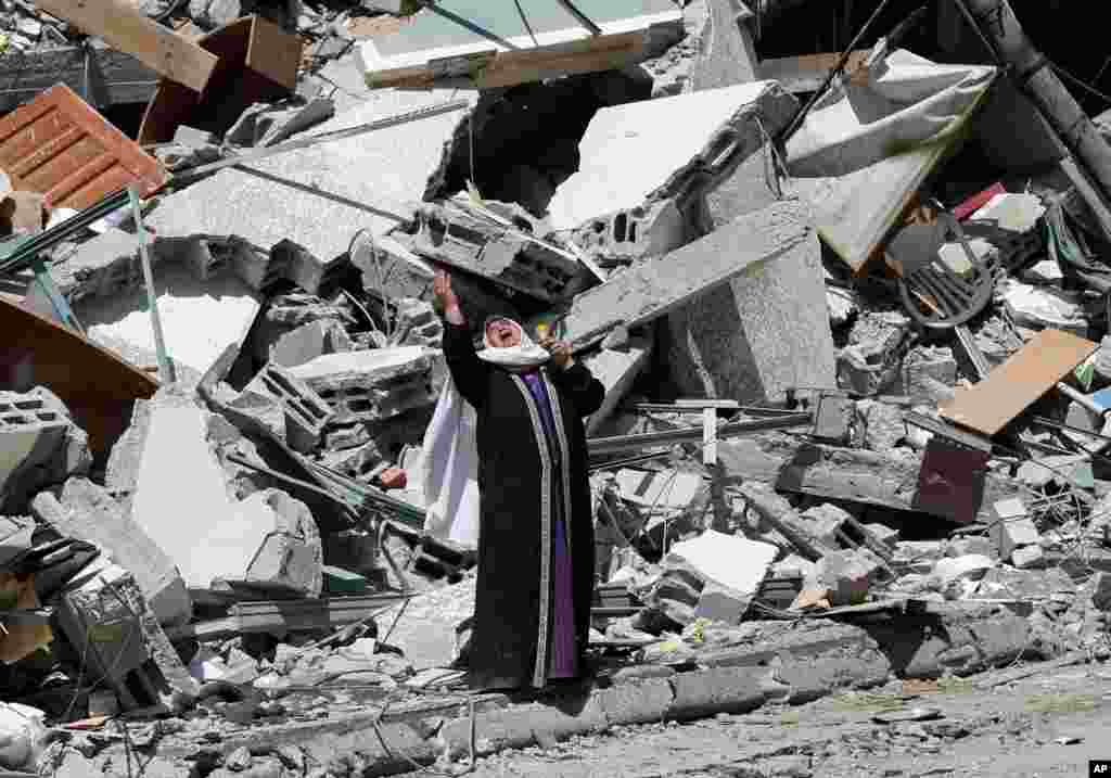 A Palestinian woman reacts near the rubble of a building housingThe Associated Press, broadcaster Al-Jazeera and other media outlet, in Gaza City. The building was destroyed by an Israeli airstrike on Saturday.