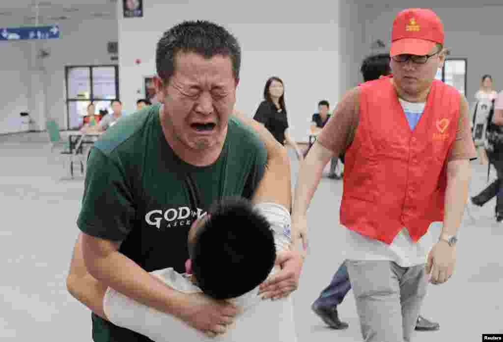 Family members cry at a caring centet for relatives of victims of a factory explosion, in Kunshan, Jiangsu province. China suffered its worst industrial accident in a year when an explosion killed at least 69 people and injured more than 120 at a factory that makes wheels for U.S. carmakers, including General Motors.
