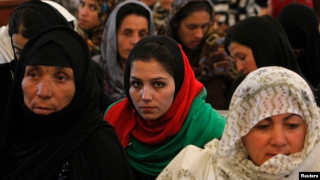 Women listen to a speech by Afghanistan's President Hamid Karzai during a district assembly gathering, in Kabul, May 30, 2013.
