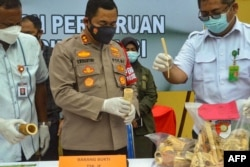 Polisi menunjukkan barang bukti berupa pipa rokok, ornamen pakaian adat dan barang koleksi dari gading gajah, di Lhokseumawe, Provinsi Aceh, 19 Agustus 2021. (AFP)