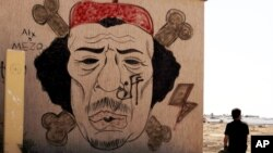 A Libyan man sits near a mural of Moammar Gadhafi, Benghazi, September 20, 2012.