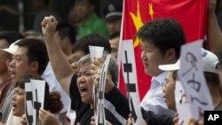 Para demonstran Tiongkok meneriakkan semboyan kemarahan anti Jepang sambil mengibarkan bendera nasional Tiongkok.