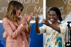 Godelieve Mukasarasi of Rwanda, holds up her award presented by first lady Melania Trump at the 2018 International Women of Courage awards, March 23, 2018, at the State Department in Washington.
