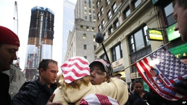Dionne Layne, facing camera, hugs Mary Power as they react to the news of the death of Osama bin Laden, May 2, 2011 in New York. At left is the rising tower, 1 World Trade Center, also known as the Freedom Tower.