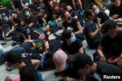 示威者2019年6月21日在香港舉行的示威活動中坐在或躺在地上,他們要求香港領導人下台並撤回引渡法案。