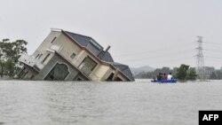 中國江西省上饒市鄱陽湖附近地區被洪水淹沒,幾人劃著小船經過一所被洪水沖倒的民宅。 (2020年7月15日)