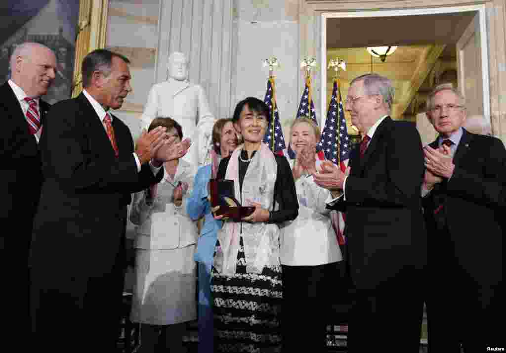 Burma's democracy leader Aung San Suu Kyi holds her Congressional Gold Medal after it was presented to her by House Speaker John Boehner (R-OH) (2nd L), at the U.S. Capitol in Washington, September 19, 2012.