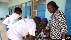 FILE - Health workers take a blood sample from a child in Gusau, northern Nigeria.